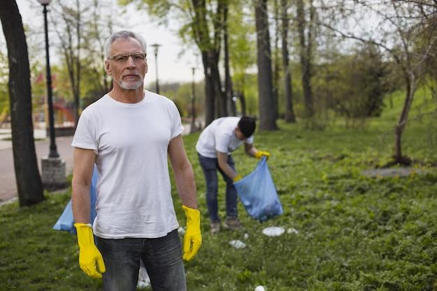 Опытный волонтер. серьезный старший волонтер в перчатках и глядя в камеру