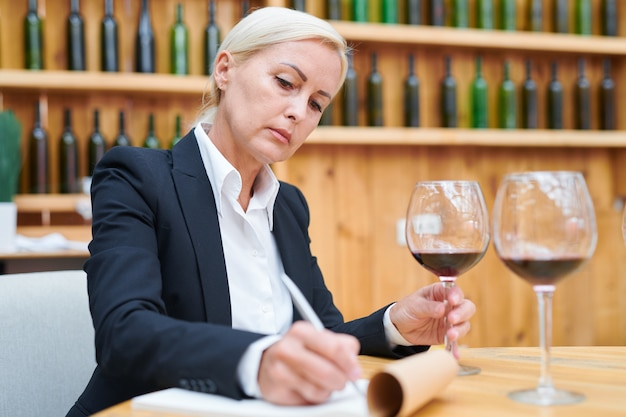 Experienced winery expert in formalwear making notes about characteristics of red wine during work in cellar