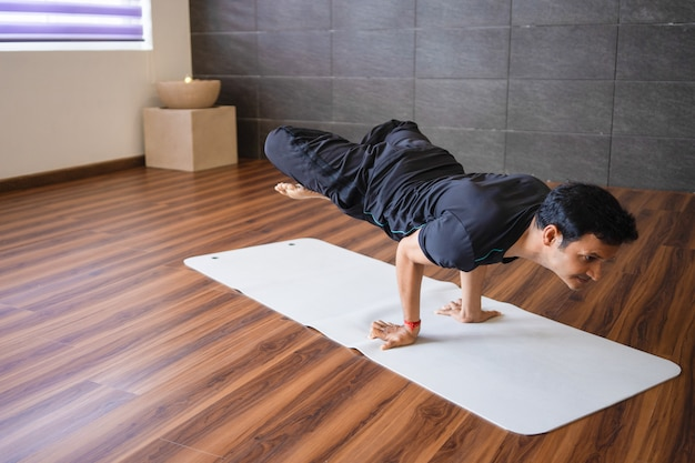 Experienced yogi doing advanced hand stand yoga pose