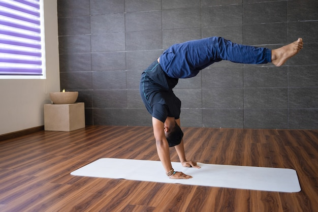 Experienced yogi doing advanced handstand yoga pose in gym