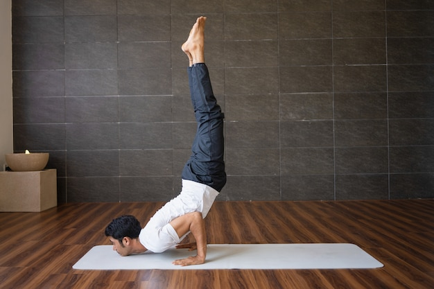 Experienced yogi doing handstand yoga pose in gym