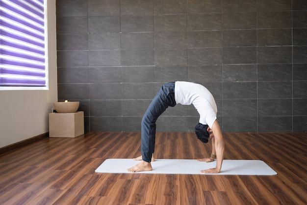 Experienced yogi doing wheel yoga pose in gym