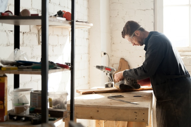 Experienced young carpenter working with wood at joinery workshop indoors
