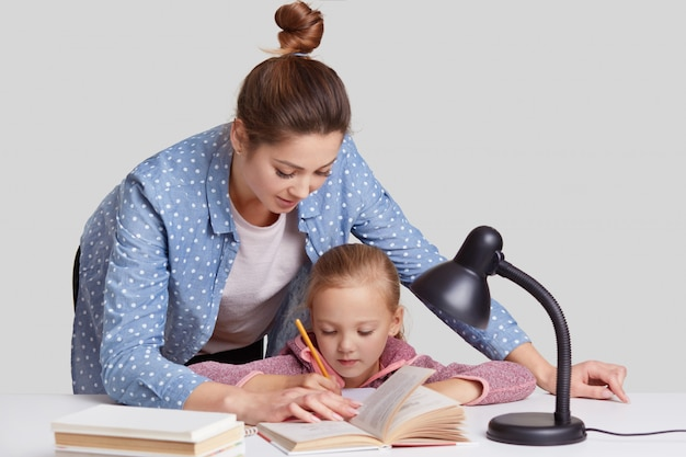 Experienced young mother leans near her small child, helps to do home assignment, shows what to rewrite in book, surrounded with reading lamp, isolated on white