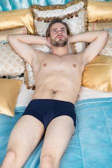 최고의 즐거움을 경험하십시오. 아침 루틴을 위해 일어나십시오. 침실에서 편안한 남자입니다. 아침에 눈을 뜬 싱글 남자. 집에서 침대에 누워 섹시 한 남자입니다. 싱글 라이프를 즐기고 있습니다. 침착하고 편안합니다.