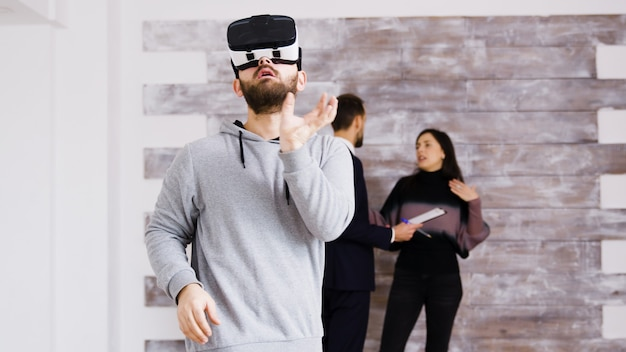 Experiencing virtual reality with headset in new apartment and woman talking with real estate agent in the background.