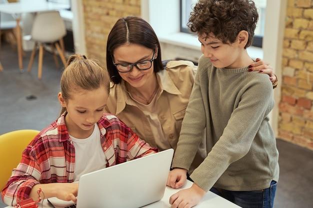 Экспериментируйте, заботливая молодая учительница в очках улыбается, помогая умным детям учиться