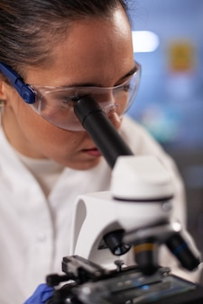 Experiment scientist analyzing sample on microscope