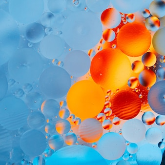 Experiment with oil drops on water. close up artful and colorful bubbles.