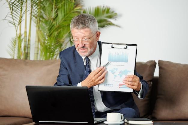 マーケティング戦略に関するオンライン会議で同僚と話すときに財務チャートを指している経験豊富な中年のビジネスマン