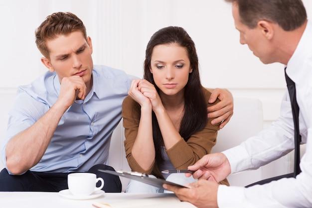 Совет эксперта. задумчивая молодая пара сидит на диване, пока уверенный финансовый консультант что-то объясняет и указывает на буфер обмена