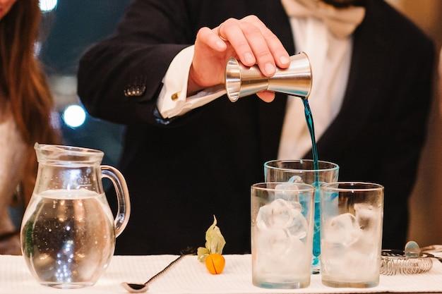 熟練したバーテンダーの手がグラスに新鮮なブルージュースを注ぎ、カクテルを作ります