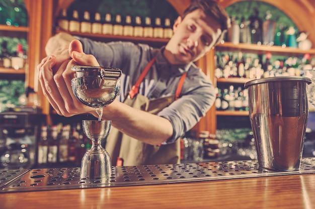 Опытный бармен делает коктейль в ночном клубе.