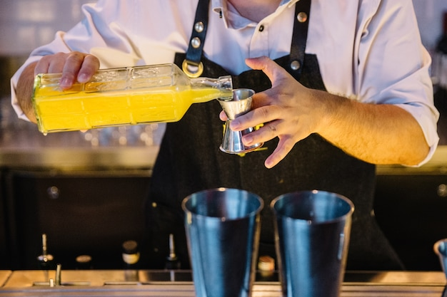 Expert barman is making cocktail with yellow juice at night club