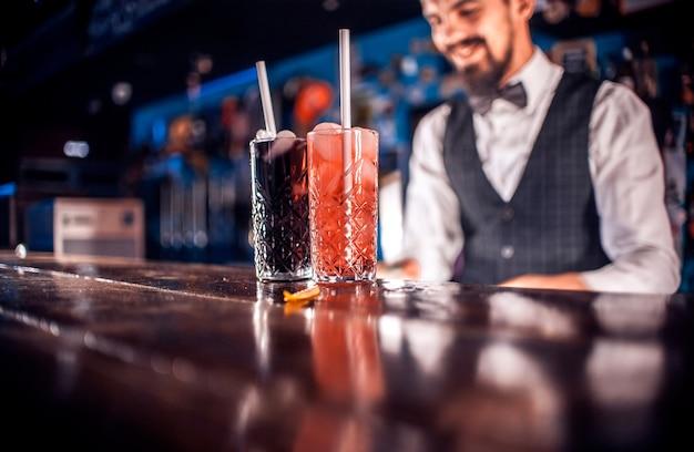 Опытный бармен устраивает шоу, создавая коктейль у стойки бара.