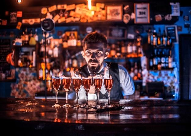 Опытный бармен напряженно дорабатывает свое творение, стоя возле барной стойки в ночном клубе.