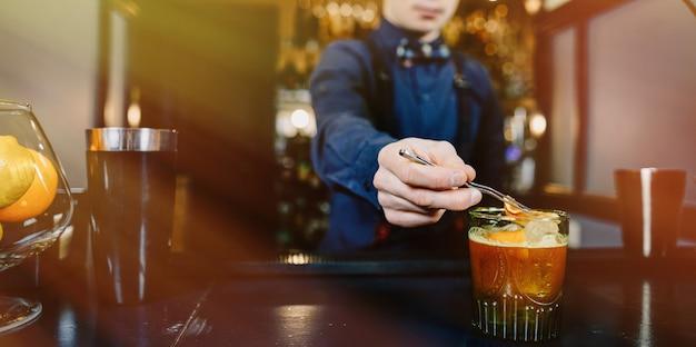 Expert bartender making cocktail at bar.