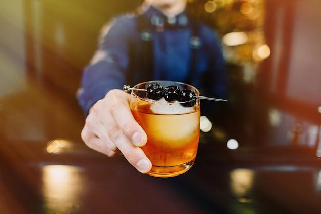 Expert bartender offering cocktail at bar.