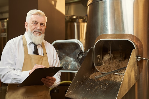 Expert of brewery standing near equipment holding folder