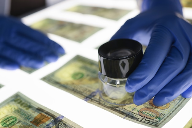 Expert checks authenticity of banknotes. counterfeiting and types of fraud concept