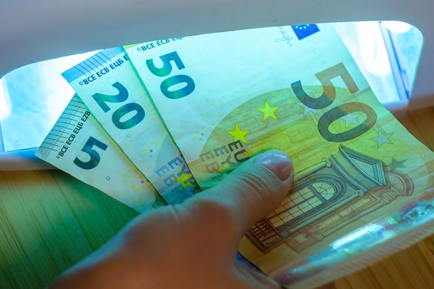 Expert checks paper euro banknotes with infrared or ultraviolet light detector.