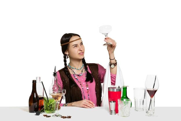 전문 여성 바텐더는 흰색 벽에 고립에서 칵테일을 만들고 있습니다. 국제 바텐더의 날, 바, 알코올, 레스토랑, 파티, 펍, 나이트 라이프, 칵테일, 나이트 클럽 컨셉