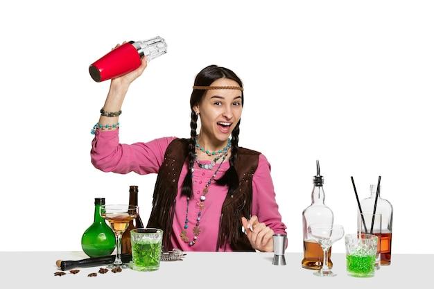전문 여성 바텐더는 흰색 배경에 고립 된 스튜디오에서 칵테일을 만들고있다. 국제 바텐더의 날, 바, 알코올, 레스토랑, 파티, 펍, 나이트 라이프, 칵테일, 나이트 클럽 컨셉