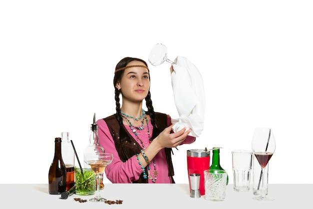 전문 여성 바텐더는 흰 벽에 고립 된 스튜디오에서 칵테일을 만들고 있습니다