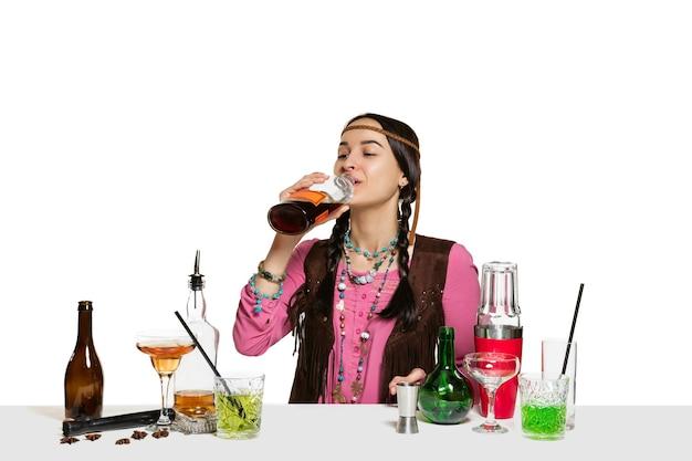 전문 여성 바텐더는 흰 벽에 고립 된 칵테일을 만들고 있습니다. 국제 바텐더 데이, 바, 알코올, 레스토랑, 파티, 펍, 나이트 라이프, 칵테일, 나이트 클럽 컨셉