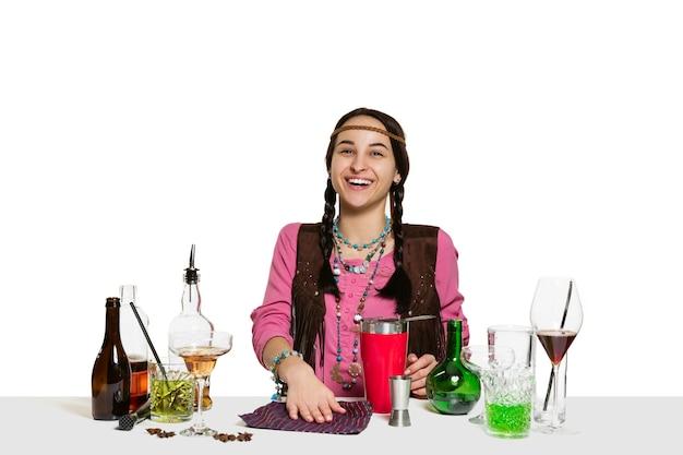 専門家の女性バーマンが白い壁に隔離されたカクテルを作っています。国際的なバーテンダーの日、バー、アルコール、レストラン、パーティー、パブ、ナイトライフ、カクテル、ナイトクラブのコンセプト