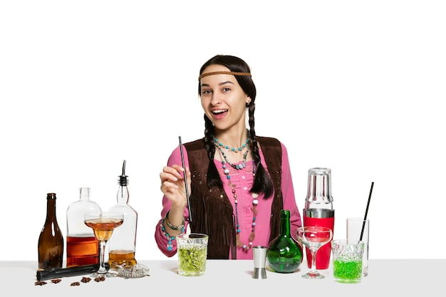 Expert female barman is making cocktail at  isolated on white wall. international barman day, bar, alcohol, restaurant, party, pub, nightlife, cocktail, nightclub concept