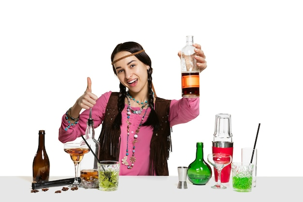 Expert female barman is making cocktail at isolated on white wall.