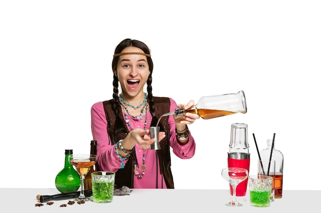 Esperto barman femminile sta preparando un cocktail in studio isolato su sfondo bianco. giornata internazionale del barman, bar, alcol, ristorante, festa, pub, vita notturna, cocktail, concetto di discoteca