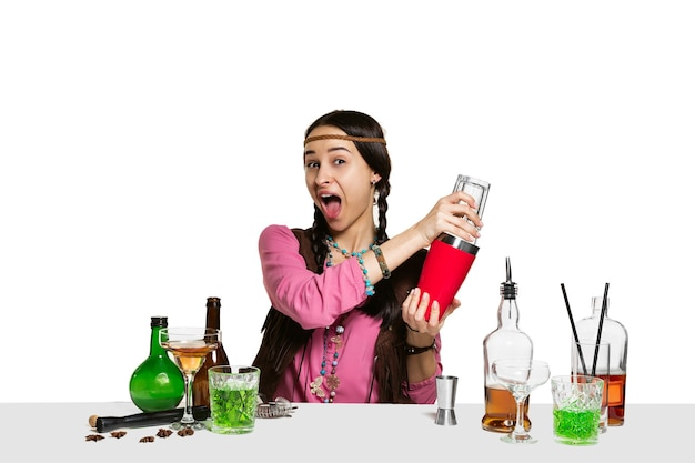 Expert female barman is making cocktail at studio