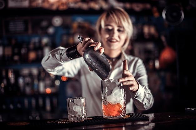 Expert girl bartender demonstrates his skills over the counter