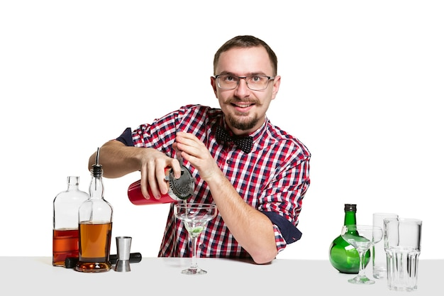 전문 남성 바텐더는 흰색 벽에 고립에서 칵테일을 만들고 있습니다. 국제 바텐더의 날, 바, 알코올, 레스토랑, 파티, 펍, 나이트 라이프, 칵테일, 나이트 클럽 컨셉