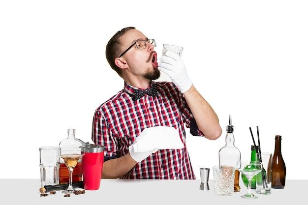 専門家の男性バーテンダーは、白い背景で隔離のスタジオでカクテルを作っています。国際的なバーテンダーの日、バー、アルコール、レストラン、パーティー、パブ、ナイトライフ、カクテル、ナイトクラブのコンセプト