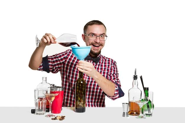 専門家の男性バーマンが白で隔離のスタジオでカクテルを作っています