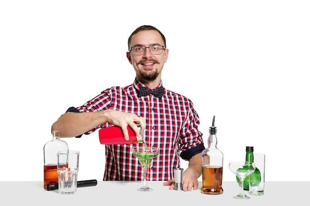 전문적인 남성 바텐더는 흰 벽에 고립 된 칵테일을 만들고 있습니다. 국제 바텐더 데이, 바, 알코올, 레스토랑, 파티, 펍, 나이트 라이프, 칵테일, 나이트 클럽 컨셉