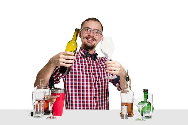 専門家の男性バーマンは、白い壁に隔離されたカクテルを作っています。国際的なバーテンダーの日、バー、アルコール、レストラン、パーティー、パブ、ナイトライフ、カクテル、ナイトクラブのコンセプト