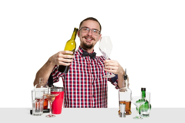 Expert male barman is making cocktail  isolated on white wall. international barman day, bar, alcohol, restaurant, party, pub, nightlife, cocktail, nightclub concept