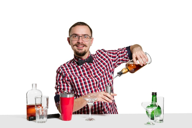 Expert male barman is making cocktail at  isolated on white wall. international barman day, bar, alcohol, restaurant, party, pub, nightlife, cocktail, nightclub concept