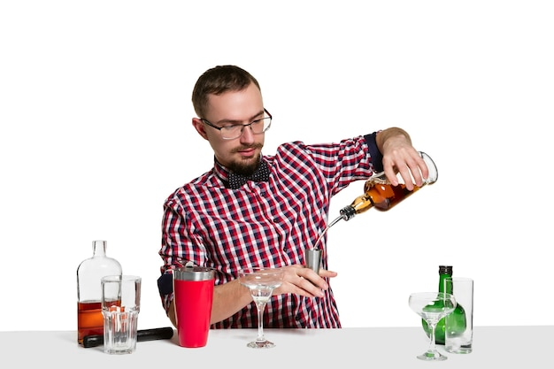 Expert male barman is making cocktail at isolated on white wall.