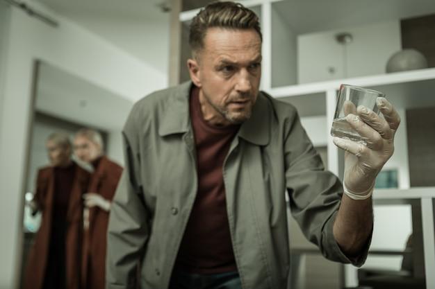 Знаток прикосновения к стеклу. нарядно одетый детектив внимательно осматривает стакан с водой с красной помадой во время тщательного обыска квартиры.
