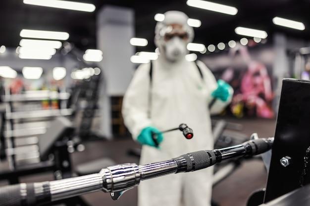 コロナウイルスの深刻な疫学的状況に関する専門家の警告。運動スペースとジム設備の清掃と消毒。防護服を着た男性が化学薬品を含む噴霧器を使用している