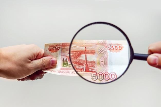 돋보기를 가진 전문가가 의심스러운 돈을 확인합니다. 위조지폐 종이에 워터마크를 검색하세요. 돋보기, 돋보기, 돋보기, 돋보기, 확대경