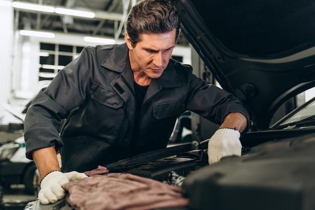 자동차 수리 서비스의 전문 자동차 정비사. 자동차 정비 및 자동 서비스 차고 개념입니다. 일하는 백인 남자