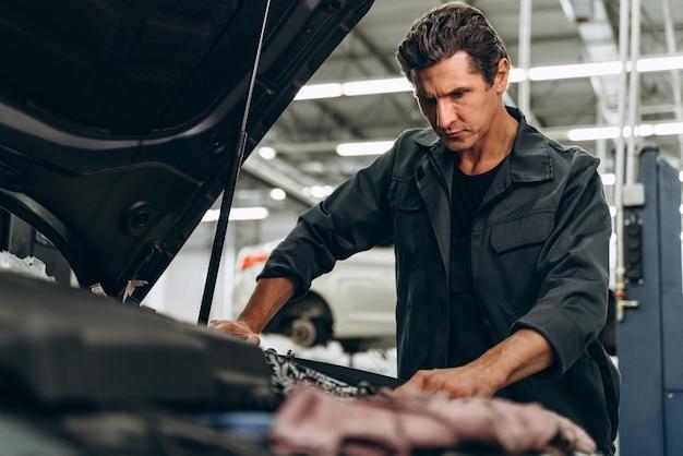 자동차 수리 서비스의 전문 자동차 정비사. 주의 깊게 일하는 백인 남자. 자동차 유지 보수 및 자동 서비스 차고 개념