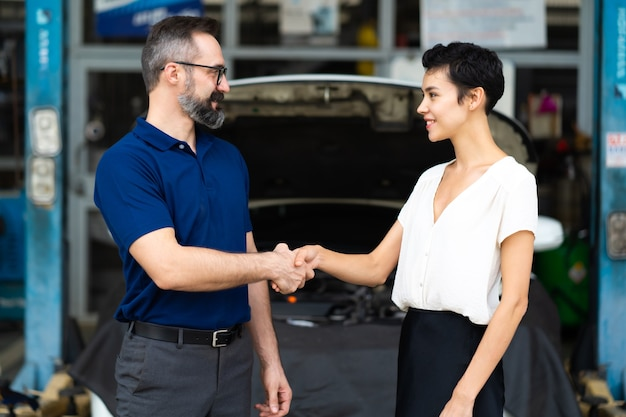 Expertise mechanic shaking hands with satisfied customer and working in automobile repair maintenance station garage. satisfaction in service.