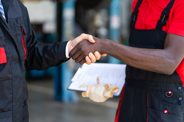 Expertise mechanic shaking hands with satisfied customer and working in automobile repair maintenance station garage